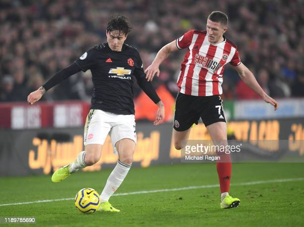 John Lundstram of Sheffield United battles for possession with Victor Lindelof of Manchester United during the Premier League match between Sheffield...