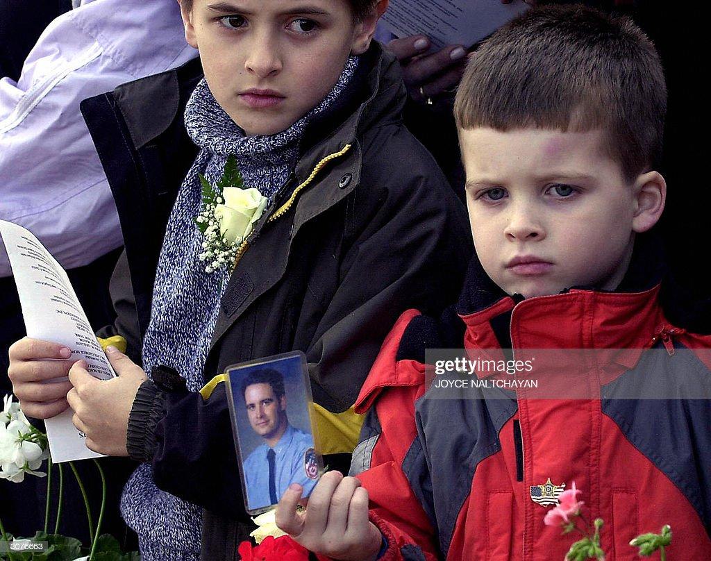 John Lynch (R), 3, holds a photo of his : News Photo
