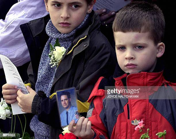 John Lynch holds a photo of his father 911 victim and New York Firefighter Michael Lynch as his brother Michael jr looks on at the Nassau County 9/11...
