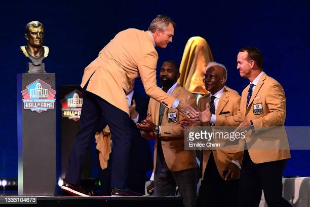 John Lynch shakes hands with Peyton Manning during the NFL Hall of Fame Enshrinement Ceremony at Tom Benson Hall Of Fame Stadium on August 08, 2021...