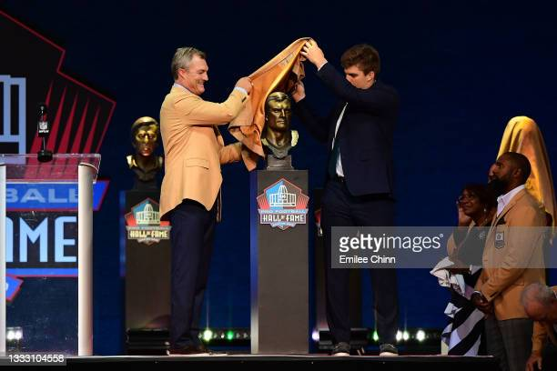 John Lynch unveils his bust with his son Jake Lynch during the NFL Hall of Fame Enshrinement Ceremony at Tom Benson Hall Of Fame Stadium on August...