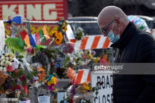 John MacKenzie, whose wife Lynn Murray lost her life in the mass shooting, reflects as he visits the temporary memorial outside of a King Soopers...