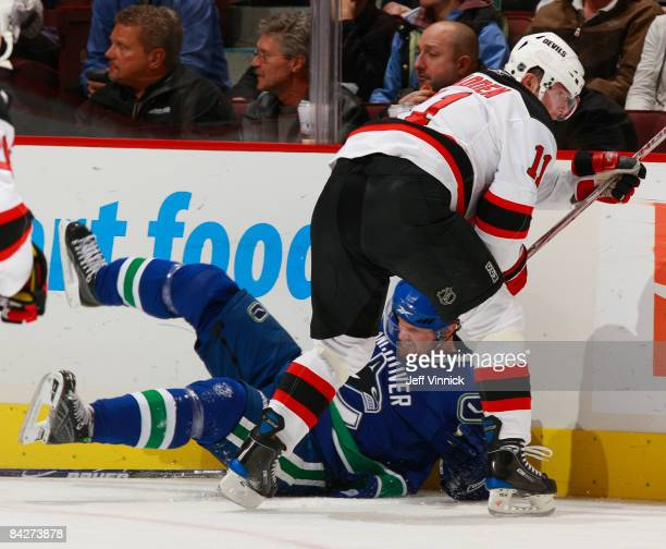 John Madden of the New Jersey Devils knocks Henrik Sedin of the Vancouver Canucks to the ice during their game at General Motors Place on January 13...