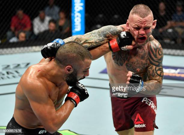 John Makdessi of Canada punches Ross Pearson of England in their lightweight bout during the UFC Fight Night event at Scotiabank Saddledome on July...