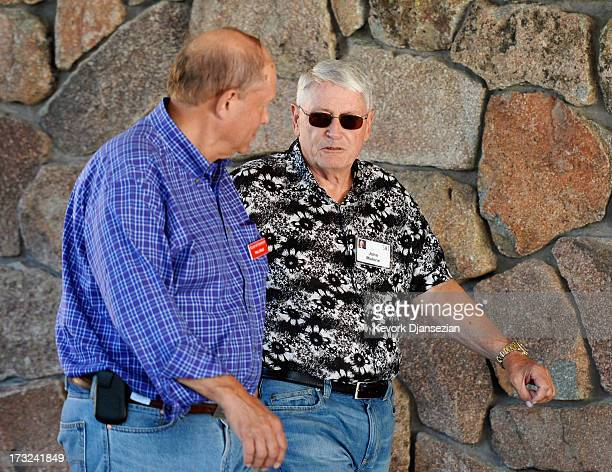 John Malone, chairman of Liberty Media and Liberty Global, and CEO of Discovery Holding Company, walks with Paul Gould, managing director of Allen &...