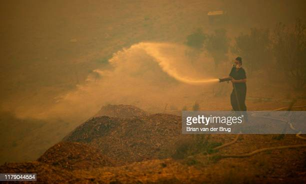 John Malta waters down mulch at his home as the Easy fire approaches October 30 2019 in Simi Valley California Fueled by the Santa Ana winds the fire...