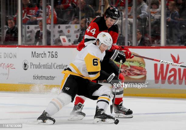 John Marino of the Pittsburgh Penguins and Miles Wood of the New Jersey Devils fight for the puck in the second period at Prudential Center on...
