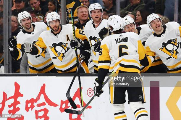 John Marino of the Pittsburgh Penguins celebrates with teammates after scoring a second period goal against Jaroslav Halak of the Boston Bruins at TD...