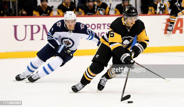 John Marino of the Pittsburgh Penguins controls the puck under pressure from Jack Roslovic of the Winnipeg Jets in the third period of the NHL debut...