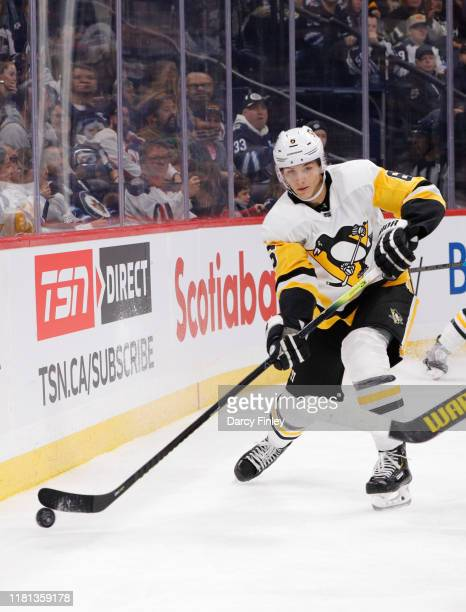 John Marino of the Pittsburgh Penguins plays the puck around the boards during third period action against the Winnipeg Jets at the Bell MTS Place on...