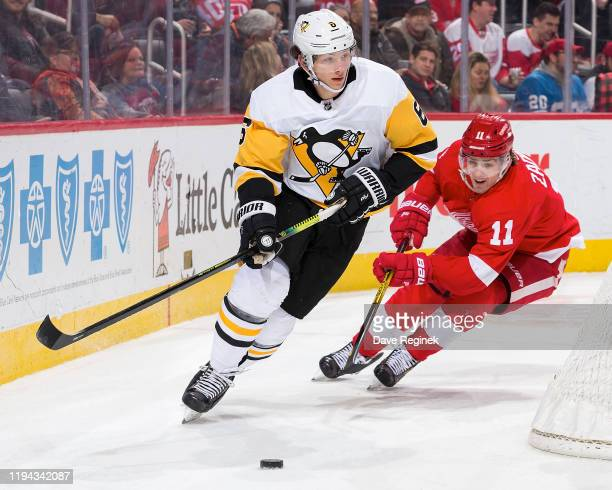 John Marino of the Pittsburgh Penguins skates with the puck behind the net followed by Filip Zadina of the Detroit Red Wings during an NHL game at...