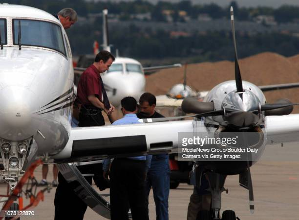 John Mark Karr red shirt is escorted off of a plane at Stevens Aviation at Jeffco Airport by officers to a waiting black suburban for transportation...