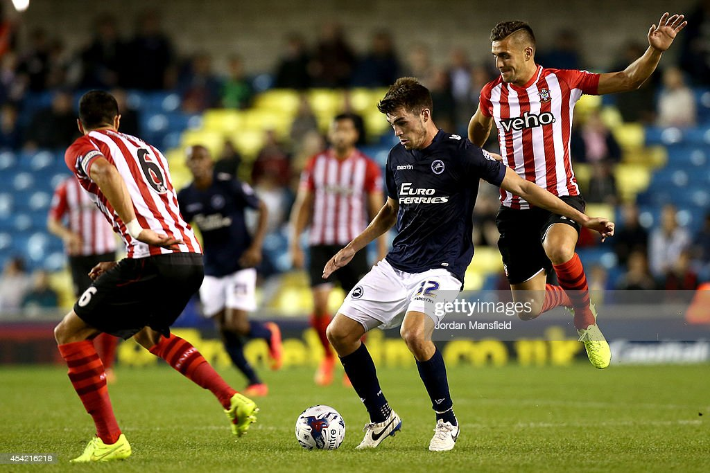 John Marquis (R) of Millwall vies with Dusan Tadic of Southampton during the Capital One Cup Second Round match between Millwall and Southampton at The Den on August 26, 2014 in London, England.