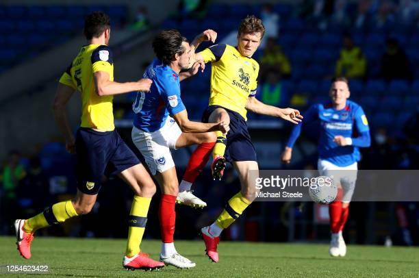 John Marquis of Portsmouth is challenges by Rob Dickie of Oxford United during the Sky Bet League One Play Off Semifinal 2nd Leg match between Oxford...
