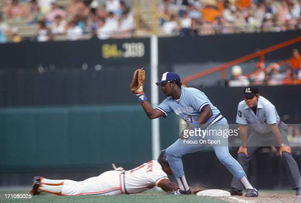 John Mayberry of the Toronto Blue Jays takes the throw over at first base as Al Bumbry of the Baltimore Orioles dives back in safe during a Major...