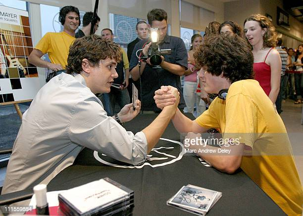 John Mayer armwrestles one of 400 fans during his private autograph session at the Virgin Megastore Boston *EXCLUSIVE COVERAGE*