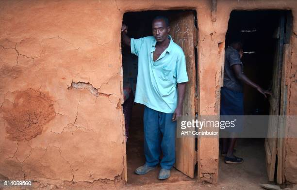 John Mbogo stands in the doorway of a mudthatch building that serves as his sons' bedroom and his wife Anne Njoki inspects an adjacent kitchen that...