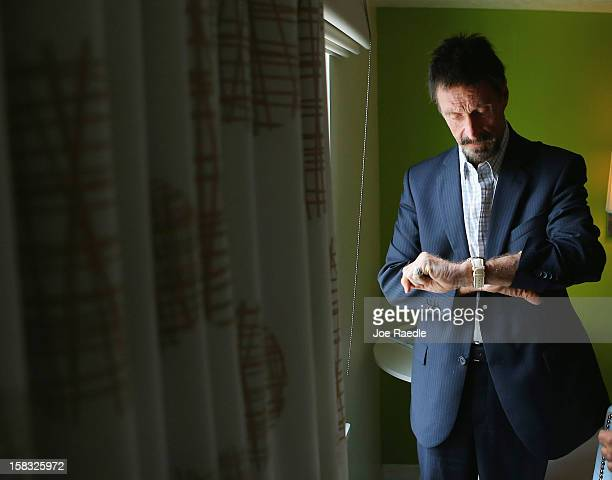 John McAfee checks his watch in his room at the Beacon Hotel where he is staying after arriving last night from Guatemala on December 13 2012 in...