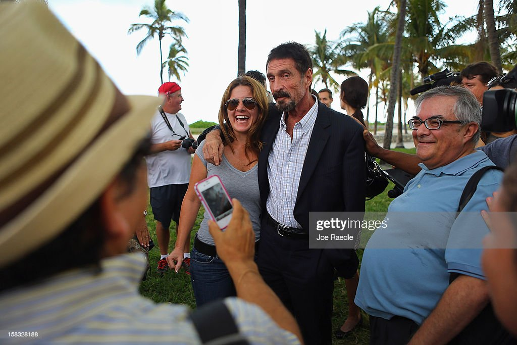 John McAfee (C) interacts with people after speaking to reporters outside of the Beacon Hotel where he is staying after arriving last night from Guatemala on December 13, 2012 in Miami Beach, Florida. McAfee is a 'person of interest' in the fatal shooting of his neighbor in Belize and turned up in Guatemala after a month on the run in Belize.