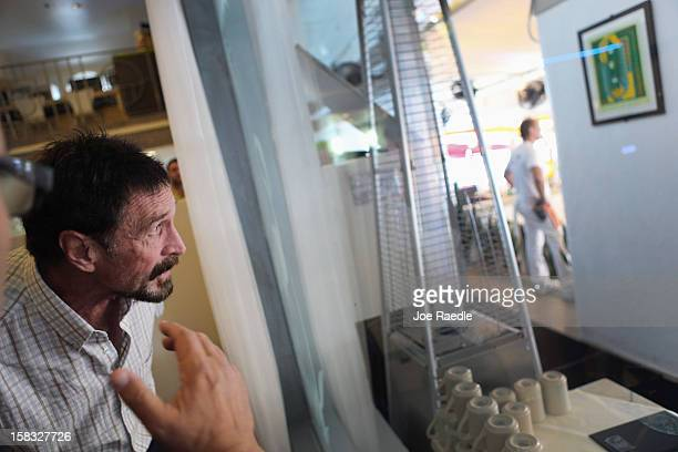 John McAfee looks out the window of the lobby at the Beacon Hotel where he is staying after arriving last night from Guatemala on December 13 2012 in...
