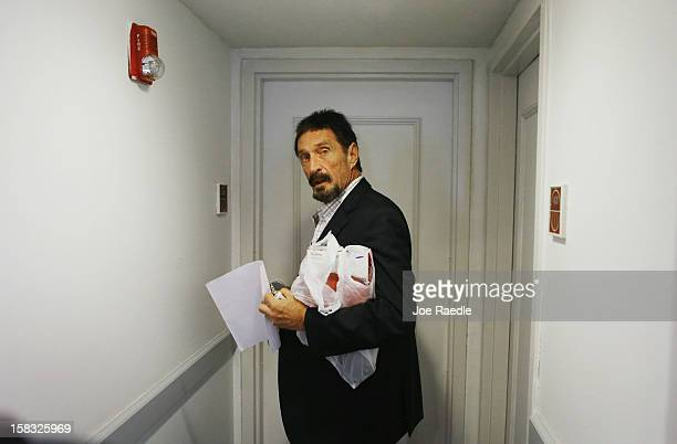 John McAfee prepares to enter his room at the Beacon Hotel where he is staying after arriving last night from Guatemala on December 13, 2012 in Miami...