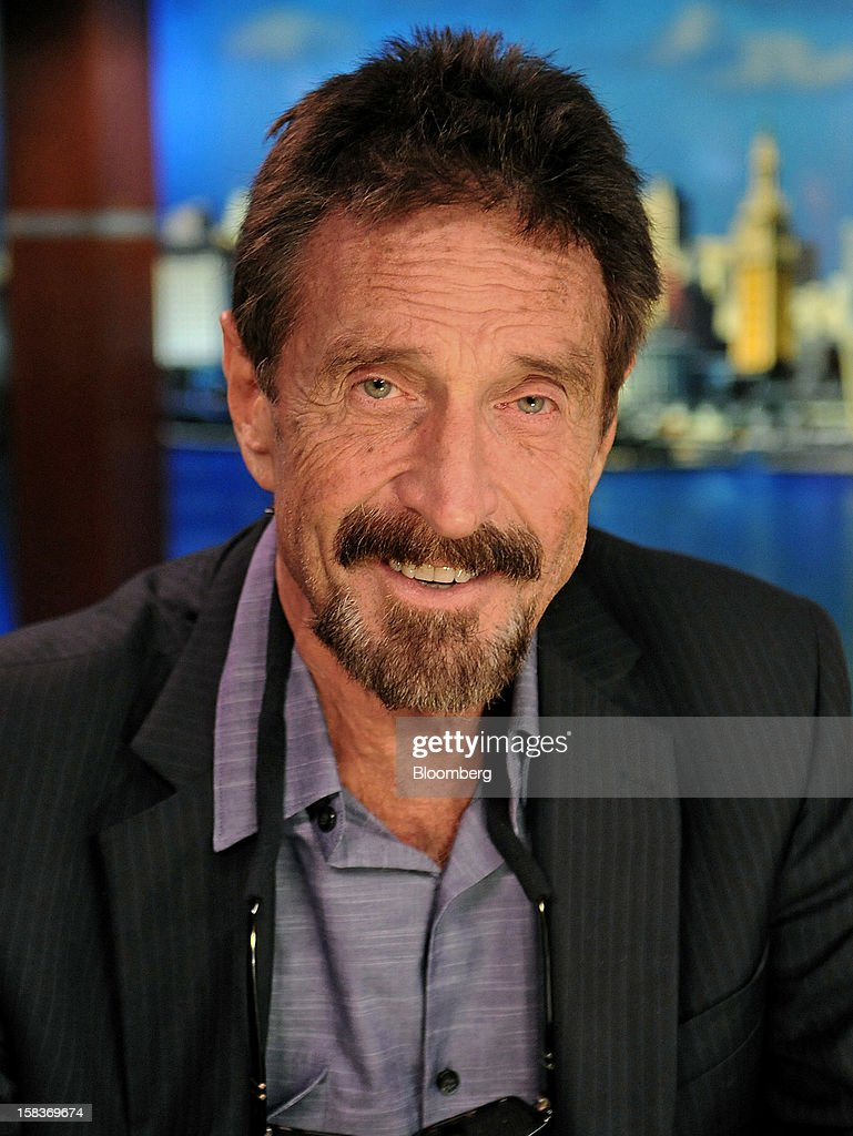 John McAfee sits for a photograph following an interview in Miami, Florida, U.S., on Friday, Dec. 14, 2012. McAfee, who is wanted for questioning in the shooting of an American citizen in Belize, was denied asylum by Guatemala. Photographer: Louis Lanzano/Bloomberg via Getty Images