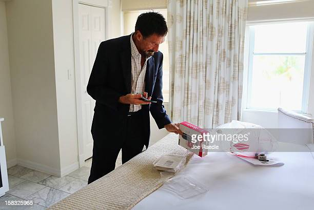 John McAfee unpacks a new cell phone in his room at the Beacon Hotel where he is staying after arriving last night from Guatemala on December 13 2012...