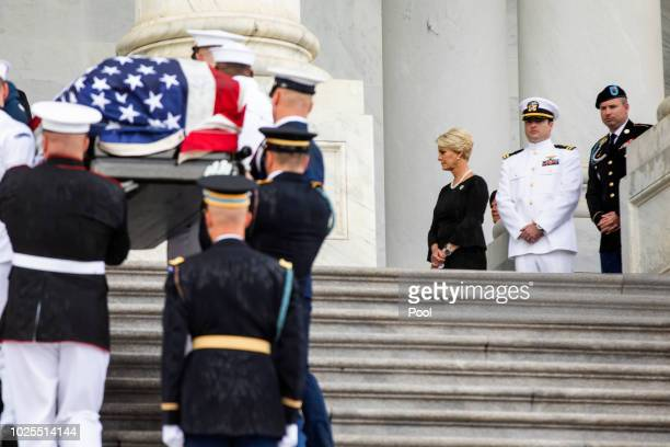 John McCain's widow Cindy McCain and his sons Jack and James watch joint service members of a military casket team carry the casket of Senator John...