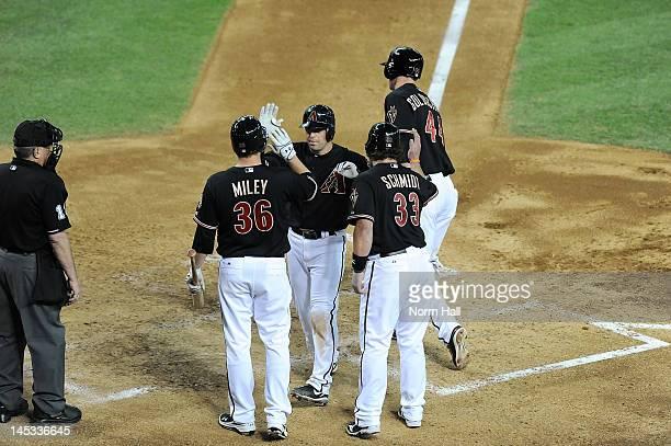 John McDonald of the Arizona Diamondbacks and teammates Wade Miley and Konrad Schmidt celebrate a three run home run against the Milwaukee Brewers at...
