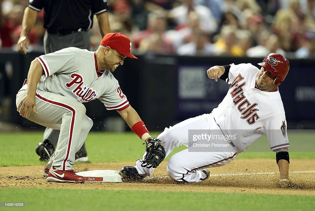 John McDonald #16 of the Arizona Diamondbacks slides in safely to third base ahead of the tag from infielder Placido Polanco #27 of the Philadelphia Phillies on a passed ball during the seventh inning of the MLB game at Chase Field on April 23, 2012 in Phoenix, Arizona.
