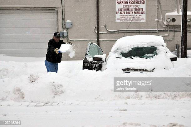 John McDonnell attempts to dig his car out by hand after a five mile wide band of lake-effect snow dumped more than two feet of snow and closed a...