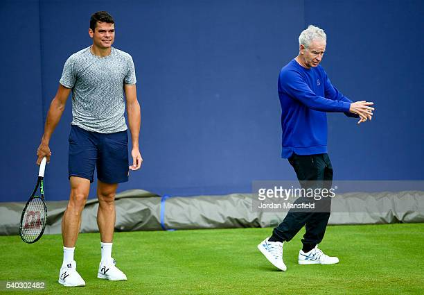 John McEnroe chats with Milos Raonic of Canada during a practice session on day one of the Aegon Championships at the Queens Club on June 13 2016 in...