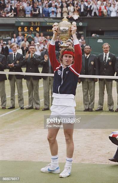 John McEnroe of the United States holds the trophy aloft after defeating Bjorn Borg during the Men's Singles Final match at the Wimbledon Lawn Tennis...