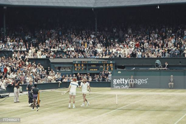 John McEnroe of the United States reaches over the net to shake hands with Bjorn Borg after defeating him during the Men's Singles Final match at the...