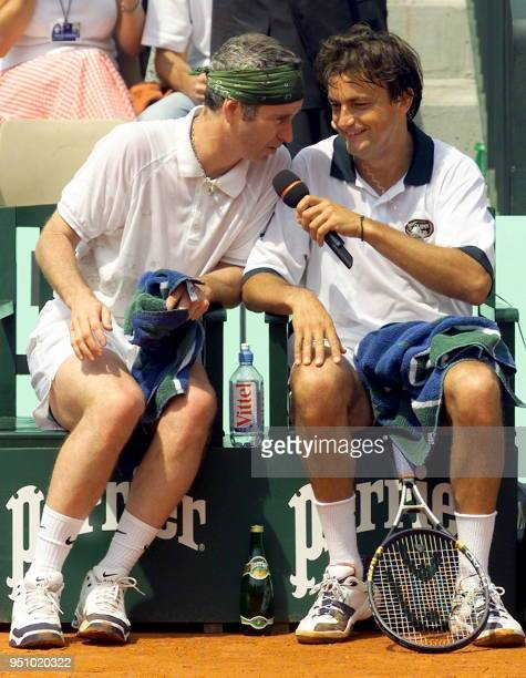 John McEnroe of the US is interviewed by his French partner Henri Leconte during a break in their under 50's Legends Trophy doubles match against...