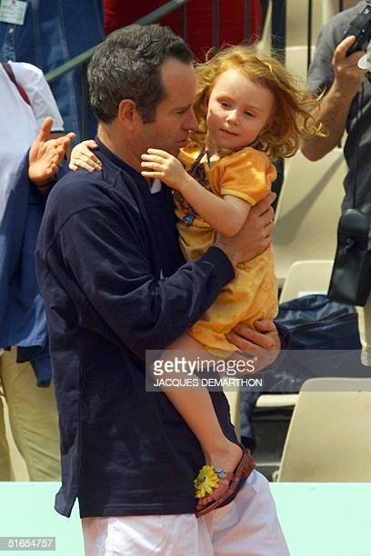 John McEnroe of the US leaves the court with his daughter Anna after he and his French partner Henri Leconte beat Bjorn Borg of Sweden and Andres...