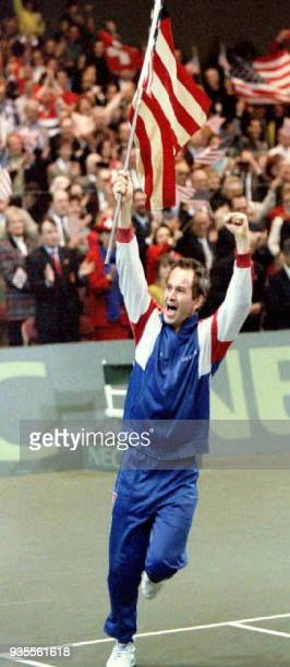 John McEnroe of the US runs around the tennis court waving the US flag 06 December 1992 after Jim Courier defeated Switzerland's Jakob Hlasek to give...