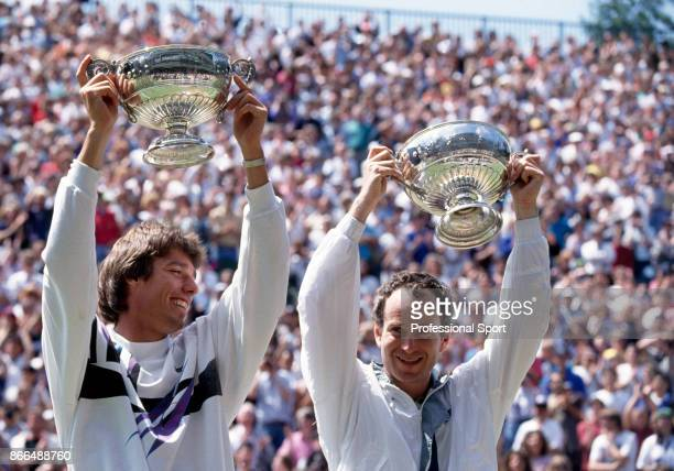 John McEnroe of the USA and Michael Stich of Germany lift their trophies after defeating Jim Grabb and Richey Reneberg both of the USA in the men's...