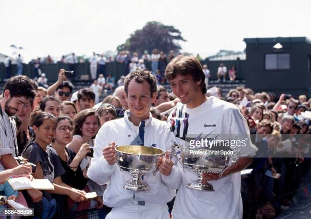 John McEnroe of the USA and Michael Stich of Germany pose with their trophies after defeating Jim Grabb and Richey Reneberg both of the USA in the...