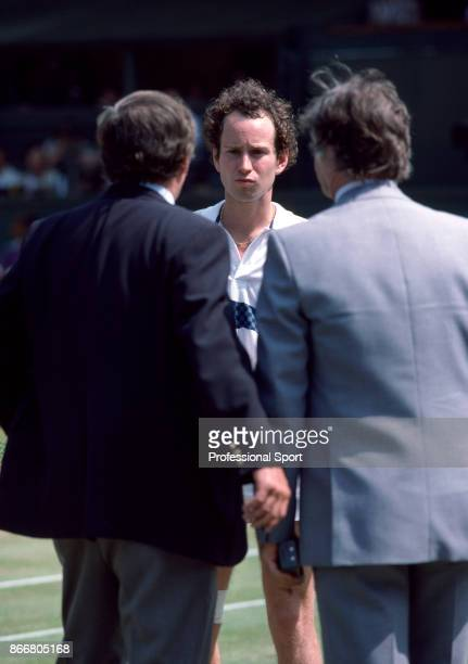 John McEnroe of the USA in discussion with officials including the tournament referee Alan Mills during the Wimbledon Lawn Tennis Championships at...