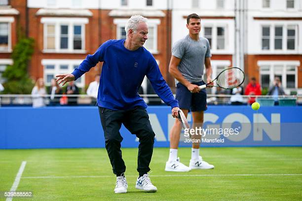 John McEnroe of the USA plays a backhand partnering Milos Raonic of Canada during a practice session during day one of the Aegon Championships at the...