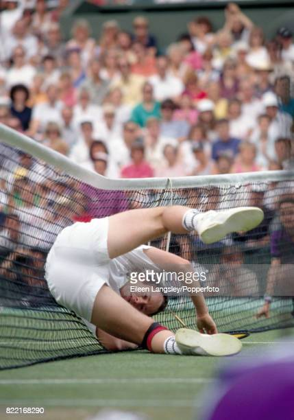 John McEnroe of the USA takes a tumble against the net during the Wimbledon Lawn Tennis Championships in London circa July 1992 McEnroe was defeated...