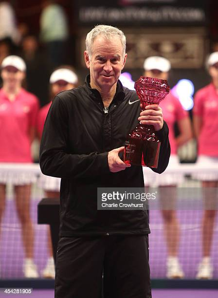 John McEnroe poses for a photograph with his trophy after winning the men's legends final against Mats Wilander of Sweden on Day Five of the Statoil...