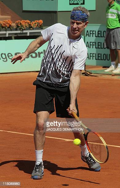 US John McEnroe returns the ball as he plays with Ecuador' Andres Gomez vs Sweden's Mats Wilander and Mikael Pernfors during legends over 45 double...