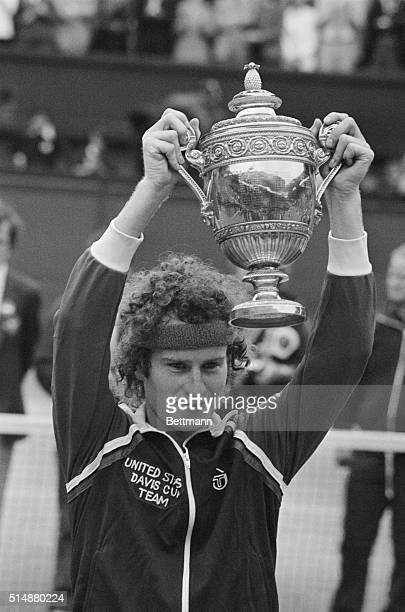 John McEnroe shows off the 1981 Wimbledon trophy to the crowds after winning the men's singles over Bjorn Borg.