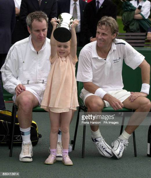 John McEnroe's daughter, four year old Anna McEnroe, holds her father's trophy for winning a charty match against Bjorn Borg at Buckingham Palace...