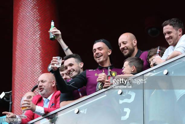 John McGinn Jack Grealish and Alan Hutton of Aston Villa celebrate promotion to the Premier League from their hotel balcony infront of fans after the...