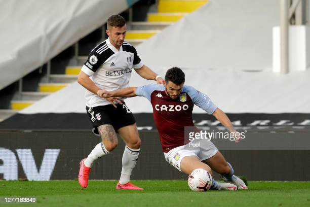 John McGinn of Aston Villa battles for possession with Joe Bryan of Fulham during the Premier League match between Fulham and Aston Villa at Craven...