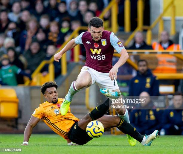 John McGinn of Aston Villa is challenged by Adama Traore of Wolverhampton Wanderers during the Premier League match between Wolverhampton Wanderers...