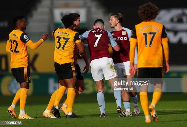 John McGinn of Aston Villa looks to calm down Jack Grealish of Aston Villa as He confronts Leander Dendoncker of Wolverhampton Wanderers and Adama...